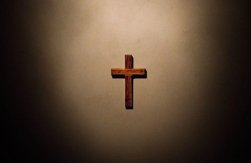 plain wooden cross in spotlight