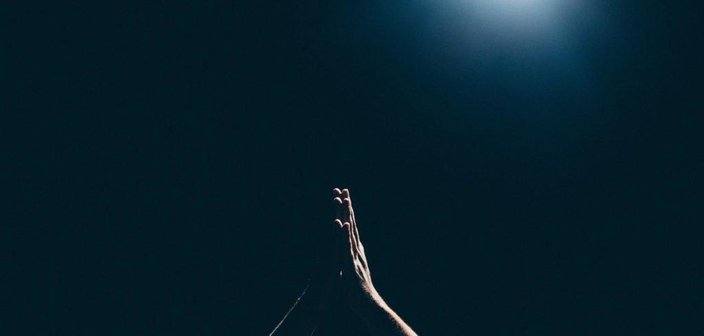 hands folded in prayer against a dark backdrop