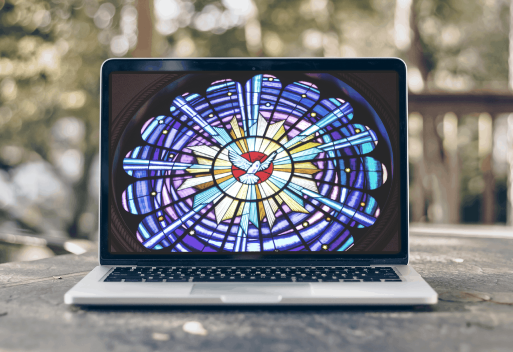 laptop computer with picture of dove in stained glass on the monitor