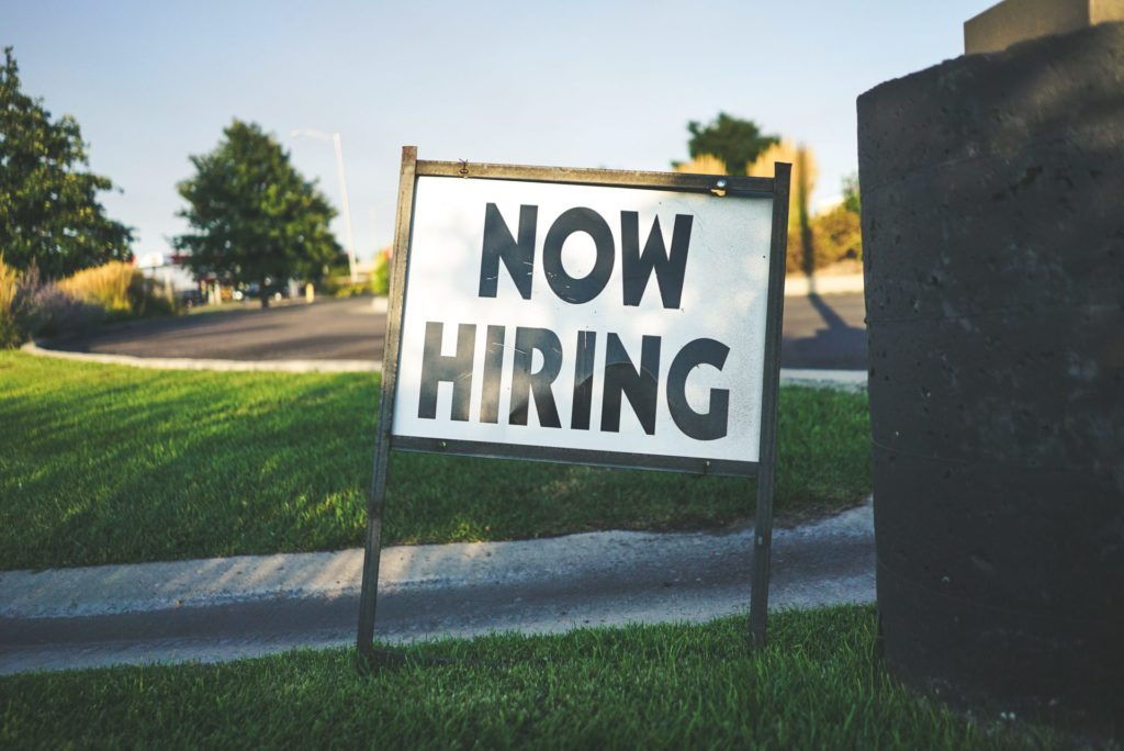 """Lawn sign that says """"Now Hiring"""""""