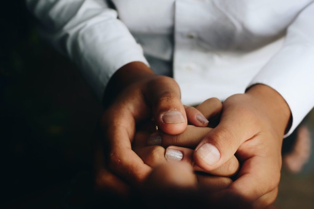 Doctor holding the hands of child patient