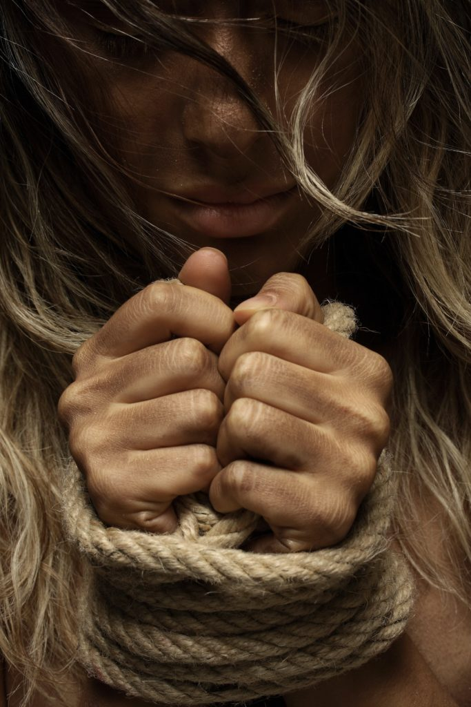 image of woman's hands bound with rope